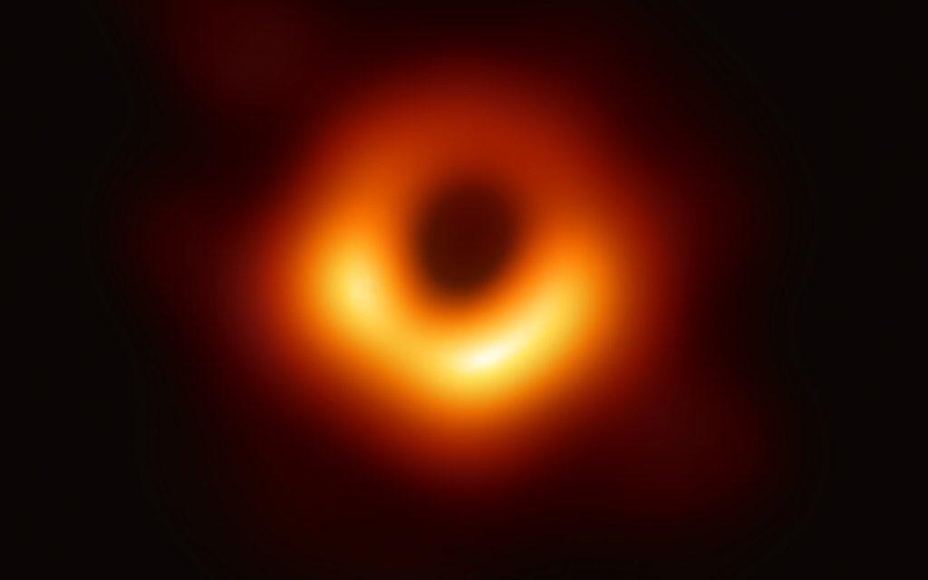 foto do buraco negro Messier 87 que parece com um círculo de fogo desfocado sobre fundo preto